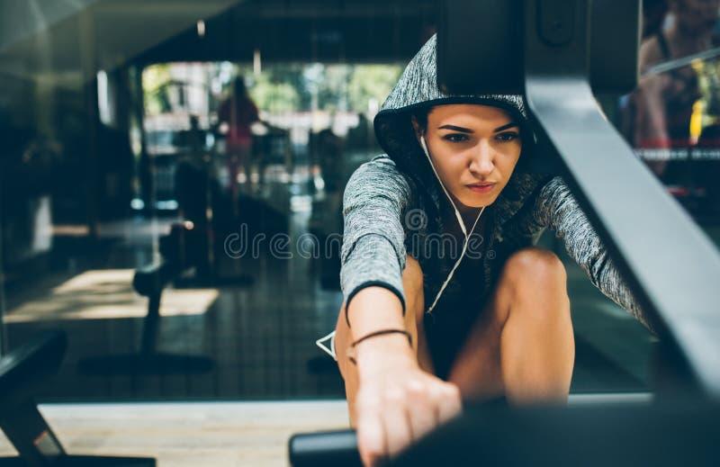 Den Caucasian färdiga brunettkvinnan gör övningar för ben i idrottshallen, den sportiga kvinnan som övar med skivstången i idrott royaltyfria bilder