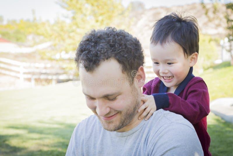 Den Caucasian fadern Having Fun med hans blandade lopp behandla som ett barn sonen royaltyfri fotografi