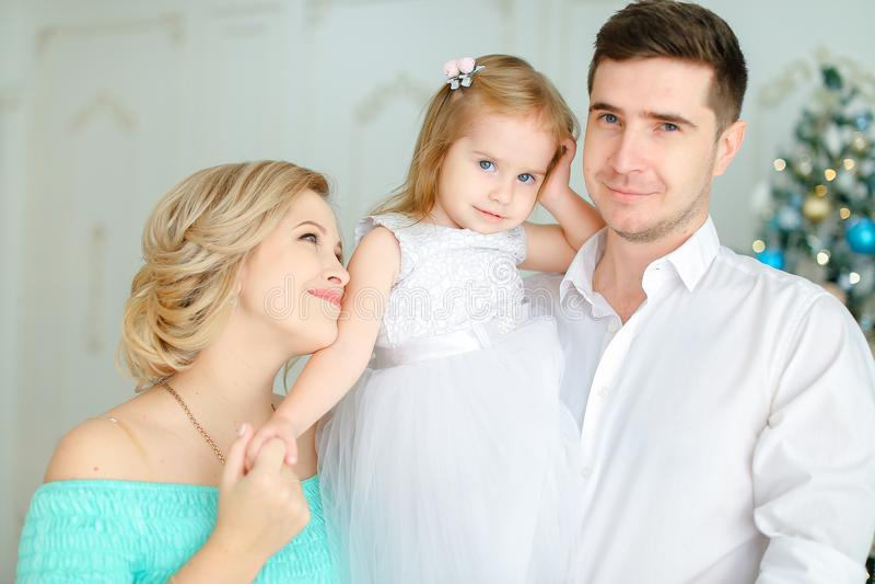 Den Caucasian fadern som håller den lilla dottern, och barnet fostrar den kyssande handen nära julgranen royaltyfri foto