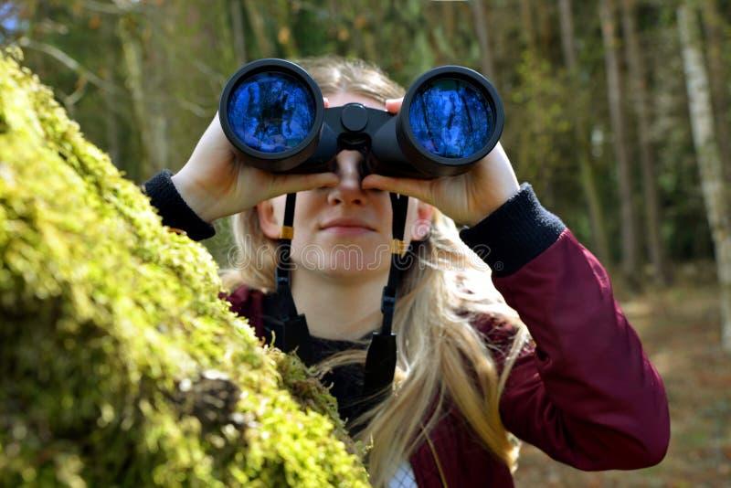 Den Caucasian flickan ser till och med kikaren arkivbilder