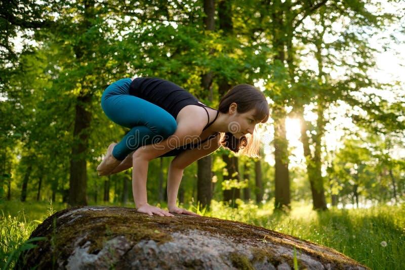 Den Caucasian flickan som gör yoga i stad, parkerar B arkivbild
