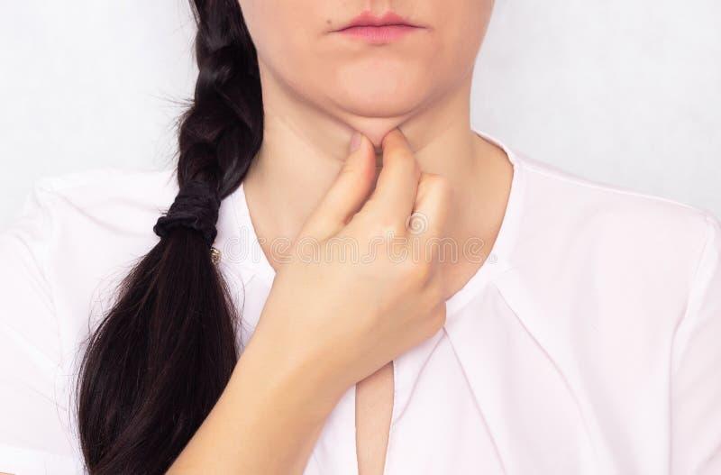 Den Caucasian härliga flickan drar hennes hand av en dubbel fet haka, ett problem med en hängande haka, vit bakgrund royaltyfria foton