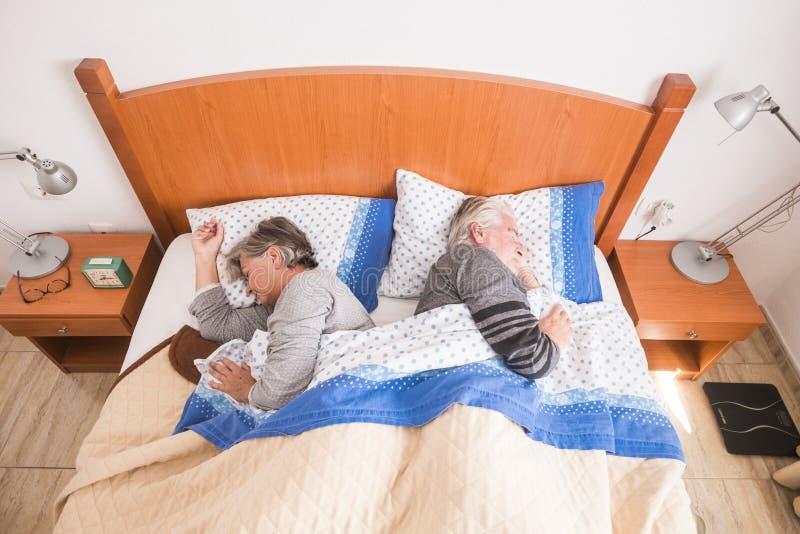 Den Caucasian höga vuxna människan åldrades par som hemma sover i morgonen i sovrummet dovided en sida varje som inte vänskapsmat arkivbilder