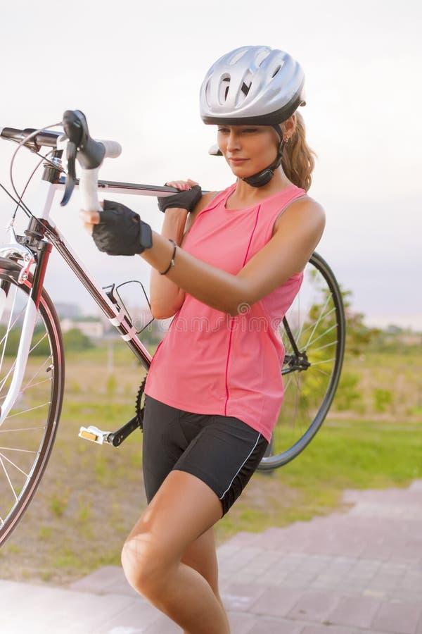 Den Caucasian idrottskvinnan utarbetar med cykeln royaltyfria bilder