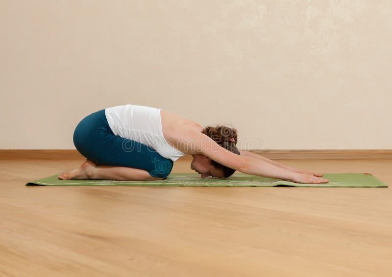 Den Caucasian kvinnan är praktiserande yoga royaltyfri foto