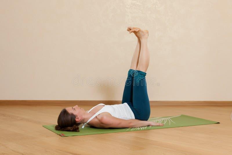 Den Caucasian kvinnan är praktiserande yoga royaltyfria bilder