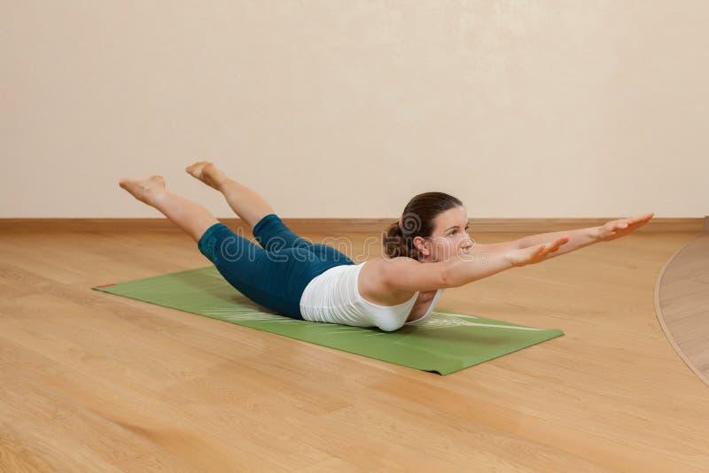 Den Caucasian kvinnan är praktiserande yoga royaltyfria foton