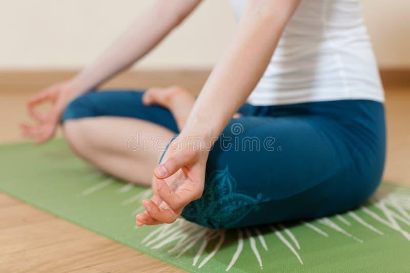 Den Caucasian kvinnan är praktiserande yoga på studion fotografering för bildbyråer