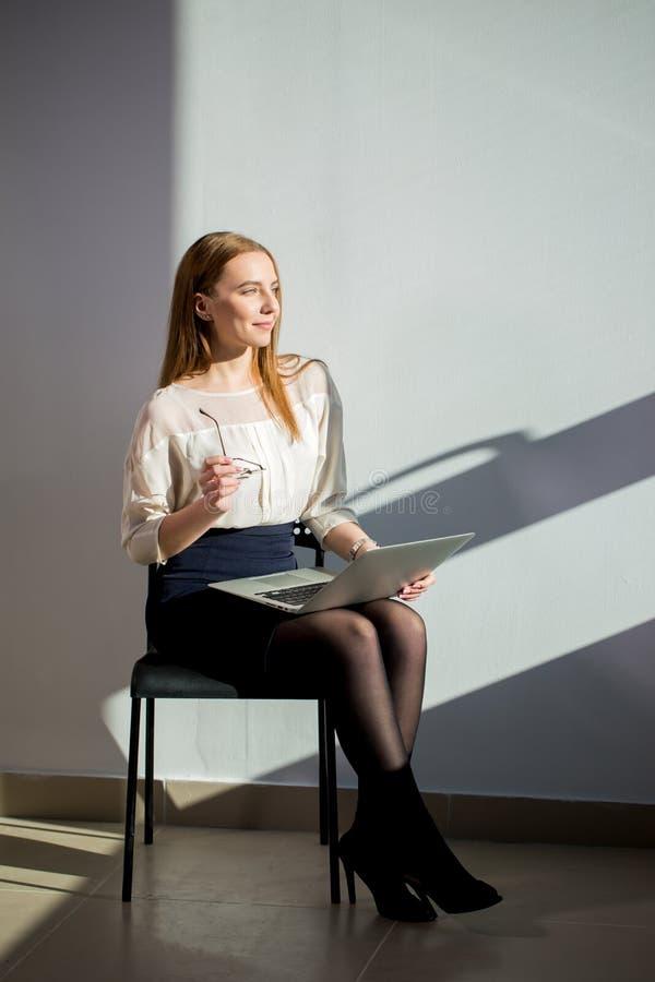 Den Caucasian kvinnan i affär beklär sammanträde på stol med bärbar datordatoren royaltyfri fotografi