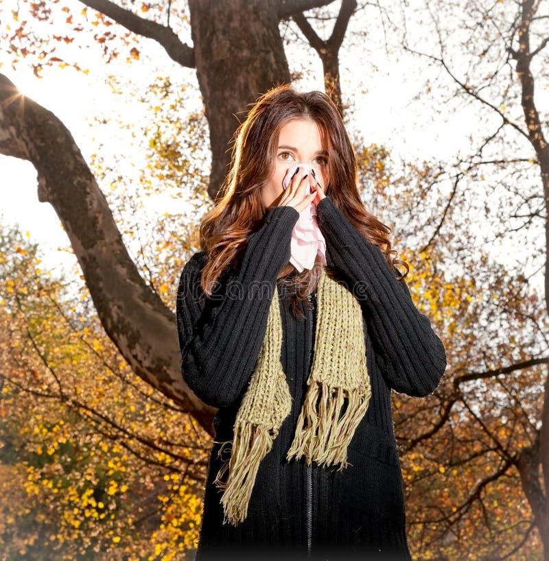 Den Caucasian kvinnan med förkylning som nyser in i silkespapper parkerar in fotografering för bildbyråer