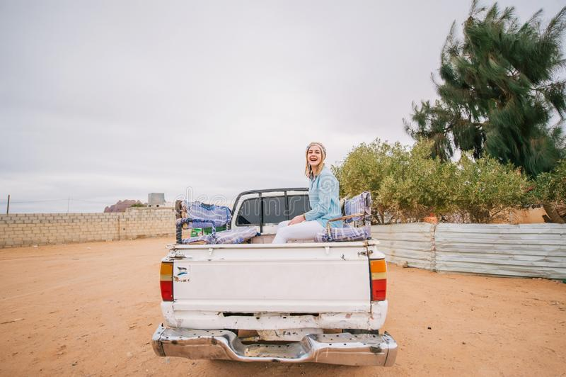 Den Caucasian kvinnan som sitter på en bil i, turnerar tid i Jordanien royaltyfri fotografi