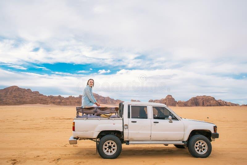 Den Caucasian kvinnan som sitter på en bil i, turnerar tid i Jordanien arkivbilder