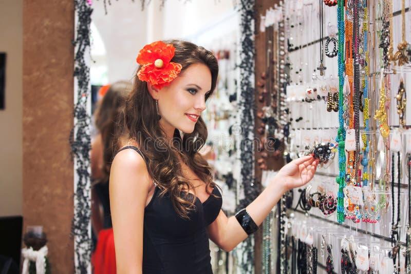 Den Caucasian kvinnan väljer smycken i shoppa arkivfoton
