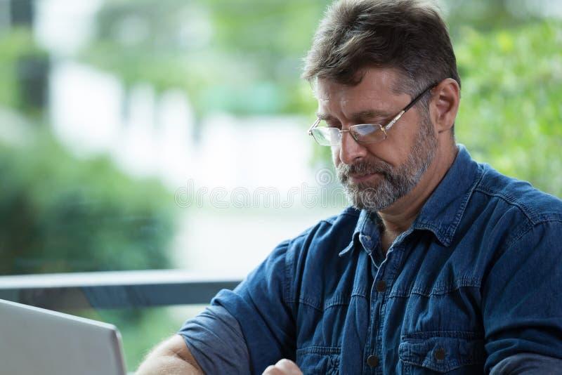 Den Caucasian mannen arbetar med en anteckningsbok fotografering för bildbyråer