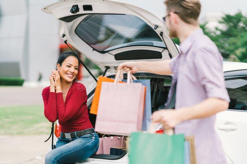 Den Caucasian mannen ger shoppingpåsar till asiatiskt kvinnasammanträde på bilen Shopaholic, förälskelse, multietniska par eller  royaltyfri bild