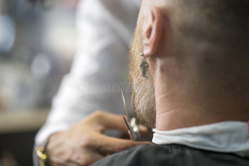 Den Caucasian mannen med det ovanliga örhänget sitter på frisersalongen medan den yrkesmässiga barberaren som klipper hans skägg arkivbilder