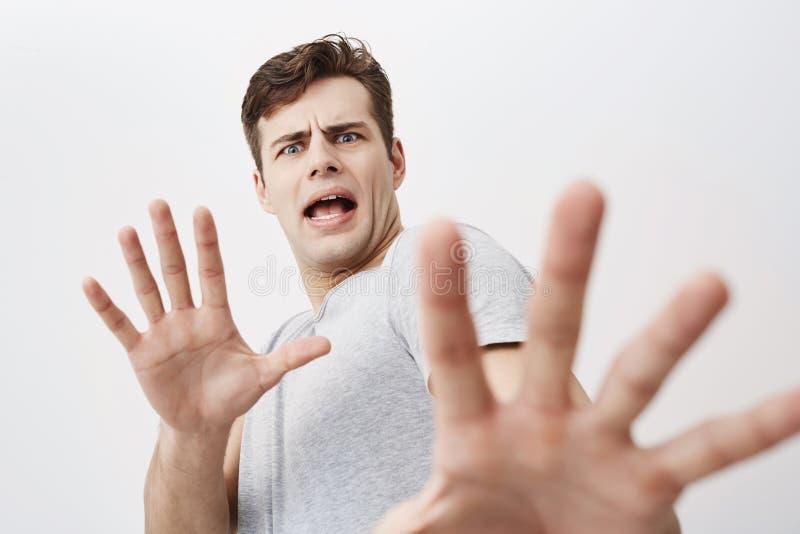 Den Caucasian mannen med förskräckt uttryck på hans skrämde gest för framsidan danande med hans gömma i handflatan som, om försök royaltyfri bild