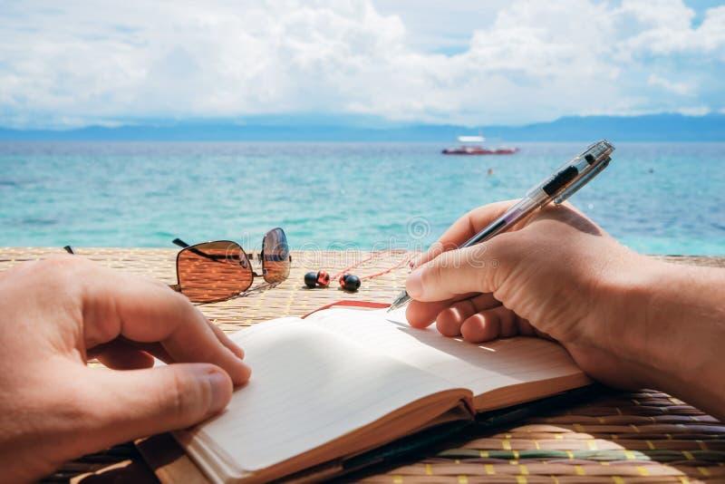 Den Caucasian mannen skrivar det simeidé, meddelandet eller brevet i hans notepad vid pennan medan honom sammanträde på stranden  royaltyfri fotografi