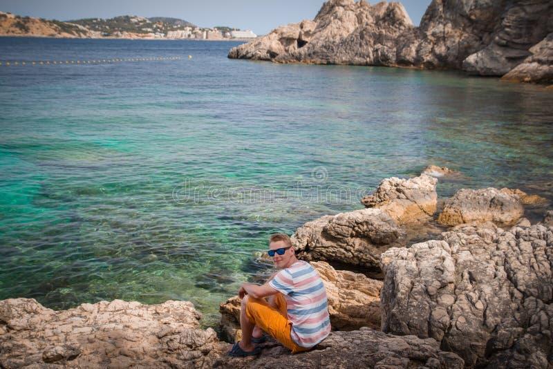 Den Caucasian mannen som b?r solglas?gon och t-skjortan som sitter p?, vaggar vid havet royaltyfri bild