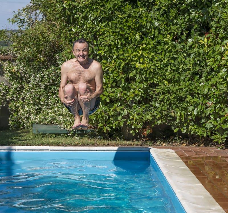 Den Caucasian mannen tar bombarderar dyk i pölen med ett roligt uttryck royaltyfri fotografi