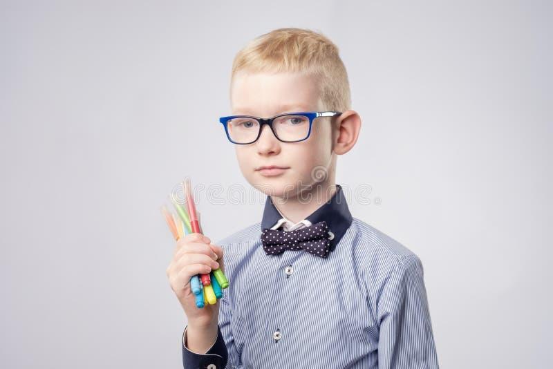 Den Caucasian pojken med innehavet för blont hår ritar, i händer och att se upp arkivbild