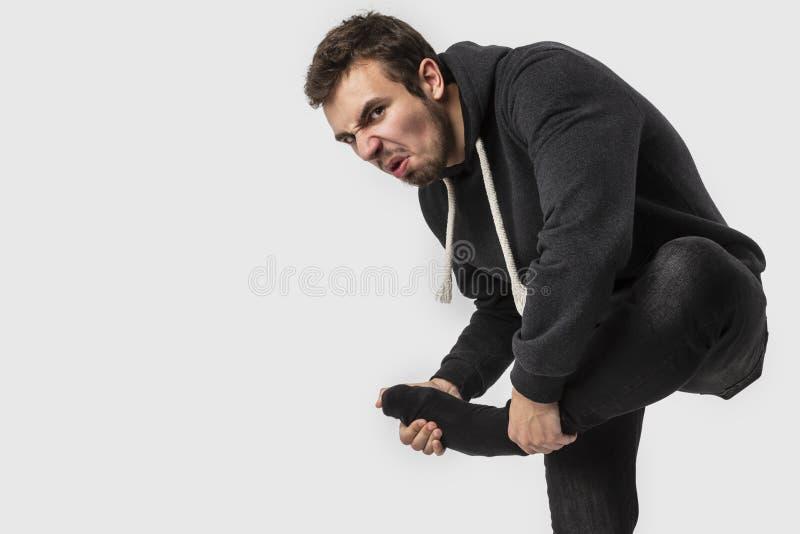 Den Caucasian unga mannen tar av hans smutsiga sockor, medan se in i kameran bakgrund isolerad white royaltyfria foton
