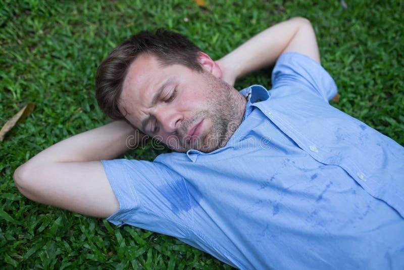 Den Caucasian unga mannen vilar på grönt gräs och ser på hans våta skjorta royaltyfri fotografi