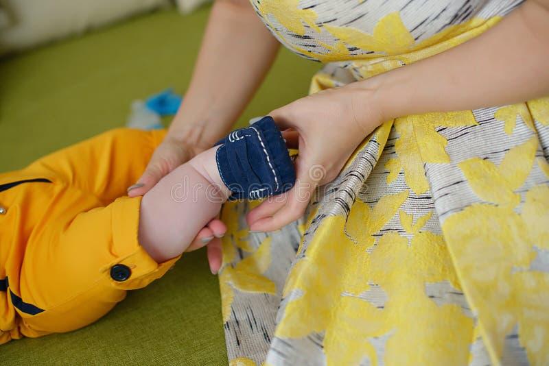 Den Caucasian unga modern som bär en gul klänning för tappning och hjälper behandla som ett barn lite, pojken som får klar arkivbild