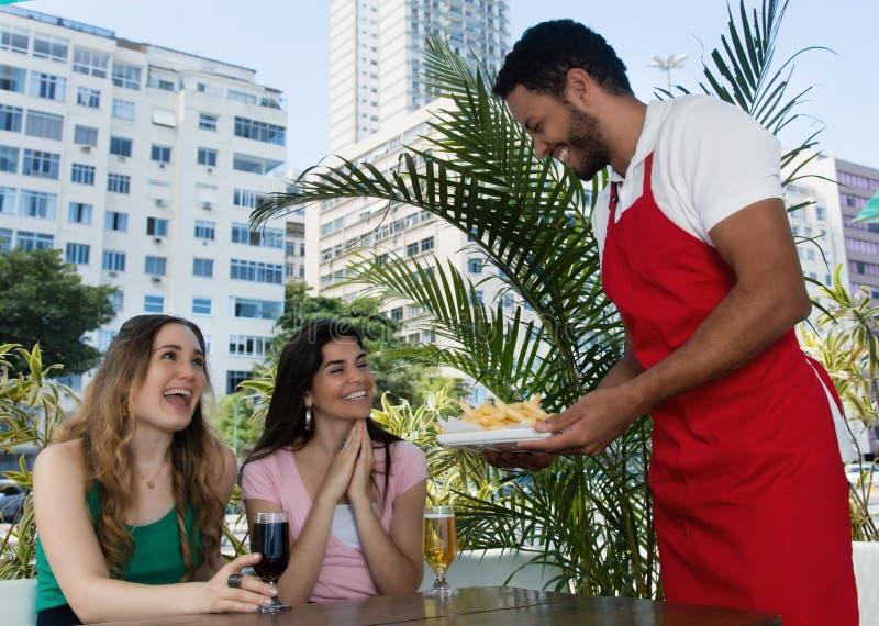Den Caucasian uppassareportionfransmannen steker till gäster i en restaurang arkivfoto