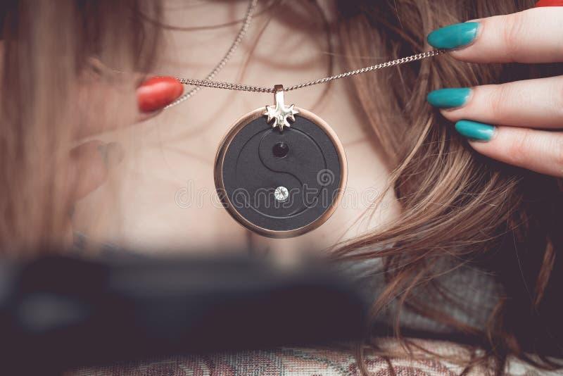 Den Chakra medaljongen som hänger på kvinna`en s, går mot arkivfoto