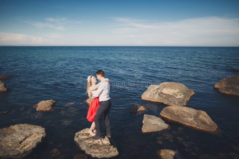 Den charmiga bruden, den eleganta brudgummen på landskap av berg och ursnyggt bröllop för havet kopplar ihop royaltyfri fotografi