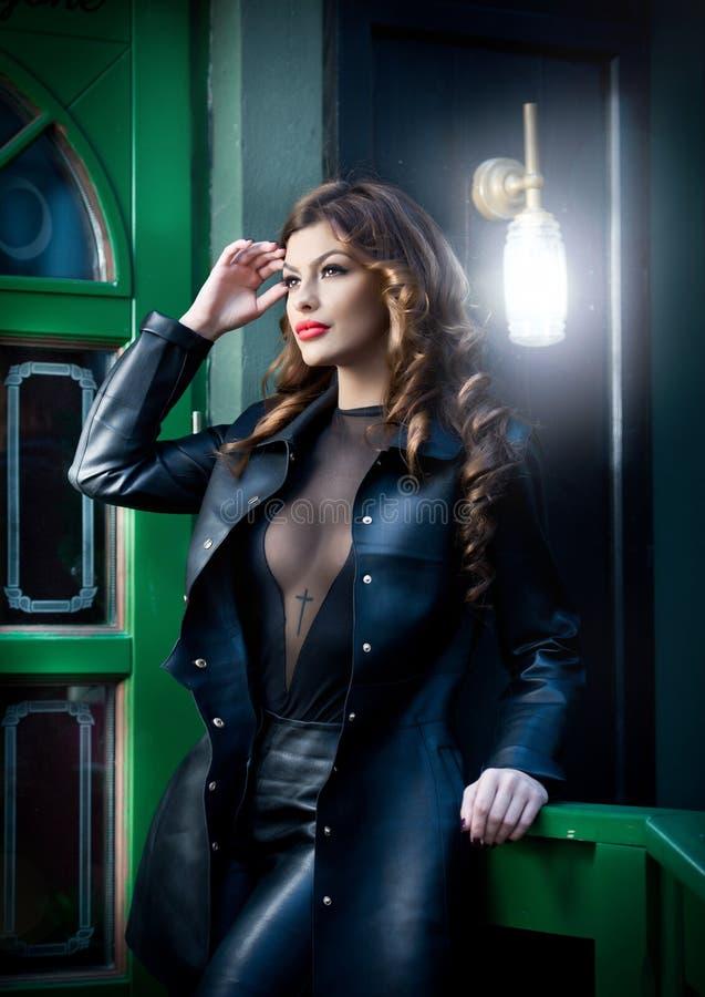 Den charmiga brunetten i svart läderdräkt med gräsplan målade dörren på bakgrund Sexig ursnygg ung kvinna med långt lockigt royaltyfria bilder
