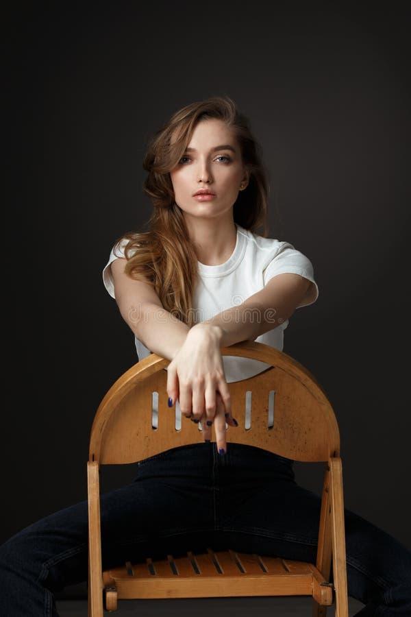 Den charmiga brunettflickan med den lång flödande t-skjortan och jeans för hår iklädda vita poserar att sitta på trästolen på arkivbilder