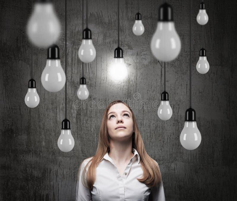 Den charmiga damen ser uppåt på de hängande ljusa kulorna ett begrepp av sökande av nya idéer royaltyfria bilder