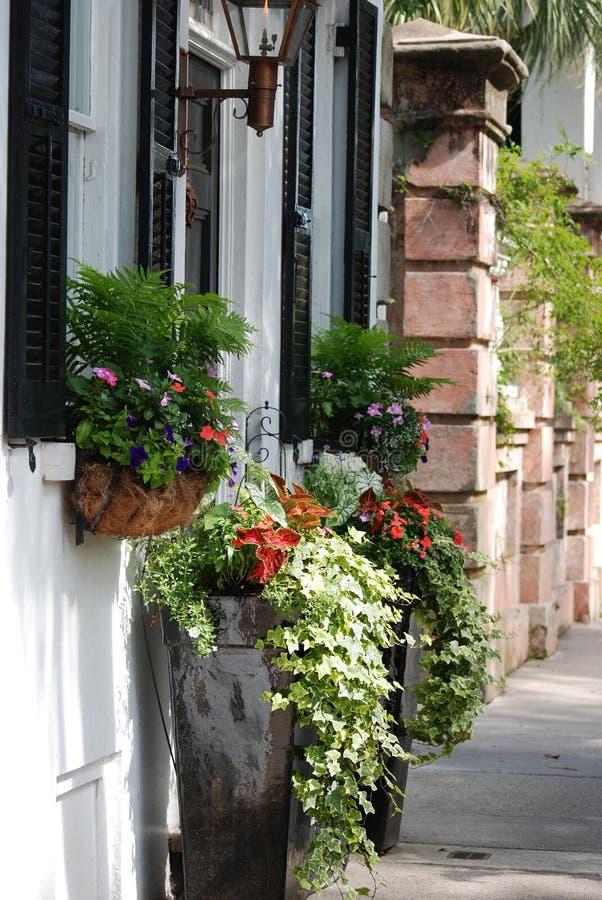 Den charmiga framdelen av huset med överloppsplanteren boxas i den i stadens centrum charlestonen, SC fotografering för bildbyråer
