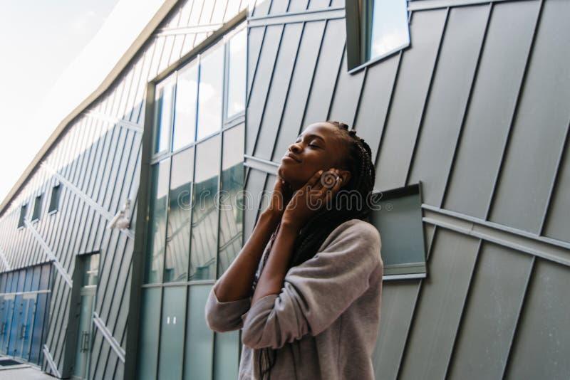 Den charmiga fridsamma afrikanska flickan med långt hår tycker om musik i hörlurar Närbildsidostående royaltyfri foto