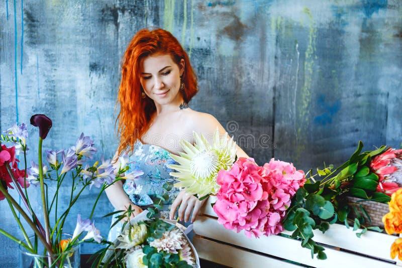 Den charmiga gladlynta röda hårkvinnlign shoppar assistentställningar vid träasken med blommor med vanlig hortensialilor, freesia arkivfoton