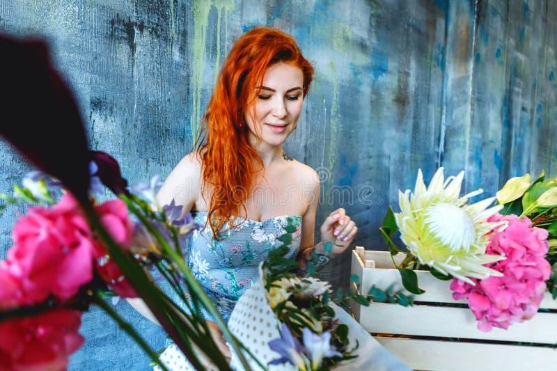 Den charmiga gladlynta röda hårkvinnlign shoppar assistentställningar vid träasken med blommor med vanlig hortensialilor, freesia royaltyfri bild