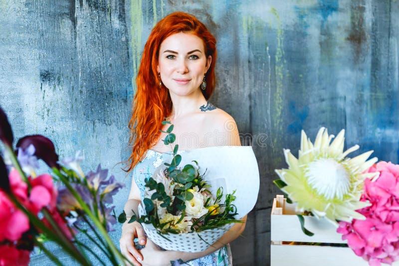 Den charmiga gladlynta röda hårkvinnlign shoppar assistentställningar vid träasken med blommor med vanlig hortensialilor, freesia arkivfoto
