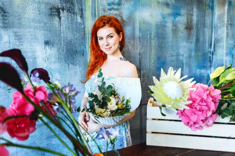 Den charmiga gladlynta röda hårkvinnlign shoppar assistentställningar vid träasken med blommor med vanlig hortensialilor, freesia arkivbilder