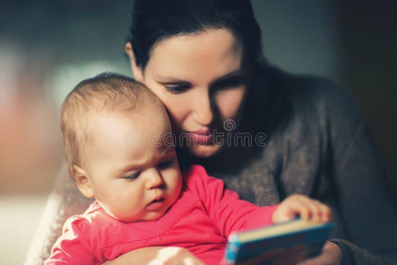 Den charmiga modervisningen avbildar i en bok till hennes gulliga litet behandla som ett barn arkivbild