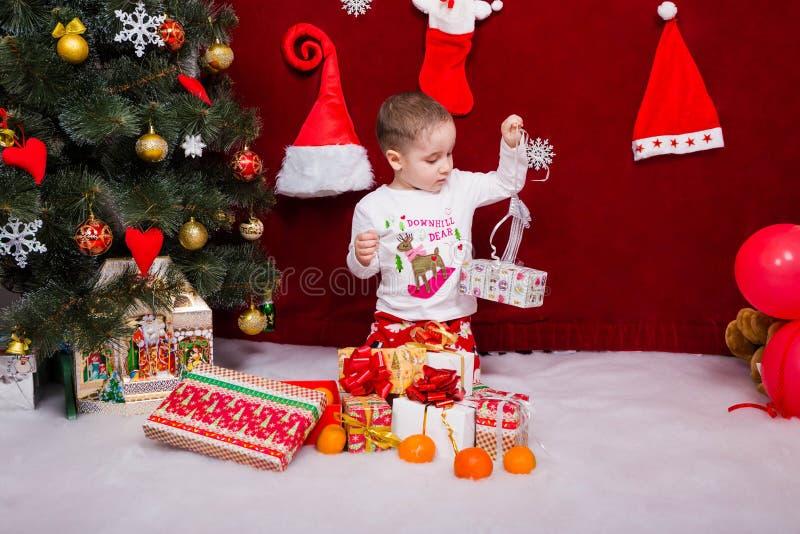 Den charmiga pojken packar upp julklappar royaltyfri fotografi