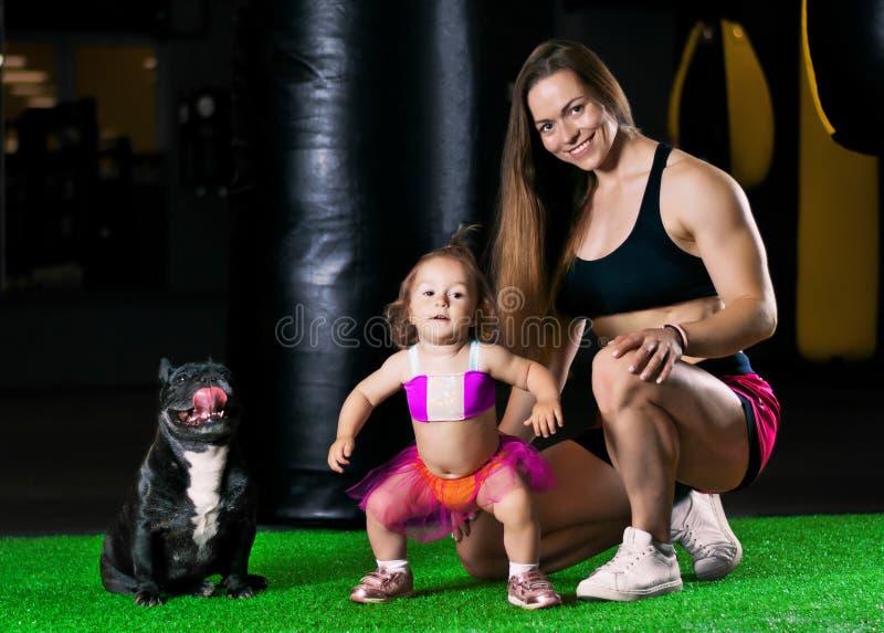 Den charmiga sportmamman utbildar i idrottshallen med hennes lilla dotter a royaltyfri fotografi