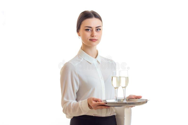 Den charmiga unga servitrins ser raksträcka och rymmer ett magasin med exponeringsglas av champagne royaltyfri fotografi