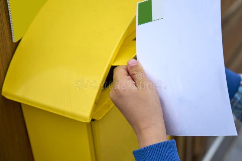 Den Childs handen sätter den tomma vykortet i en italiensk gul stolpeaskpi royaltyfri bild