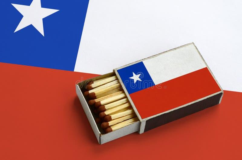 Den Chile flaggan visas i en öppen tändsticksask, som fylls med matcher och ligger på en stor flagga royaltyfria bilder