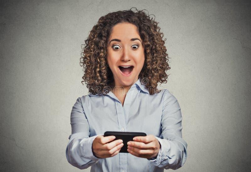 Den chockade flickan som ser telefondåliga nyheter, överraskar framsidauttryck fotografering för bildbyråer