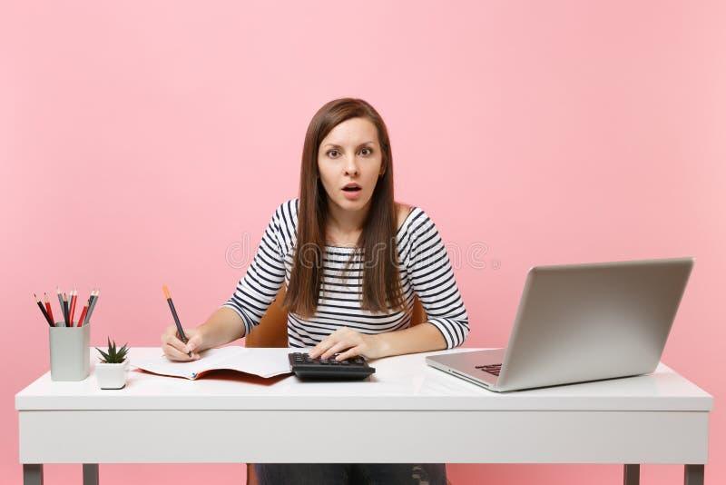 Den chockade kvinnan som använder räknemaskinen som skriver anmärkningar med beräkningar, sitter och arbetar på kontoret med den  royaltyfri foto
