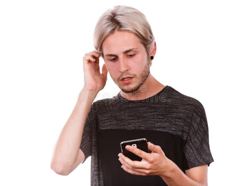 Den chockade mannen som anv?nder mobiltelefonen, l?ste meddelandet royaltyfria bilder