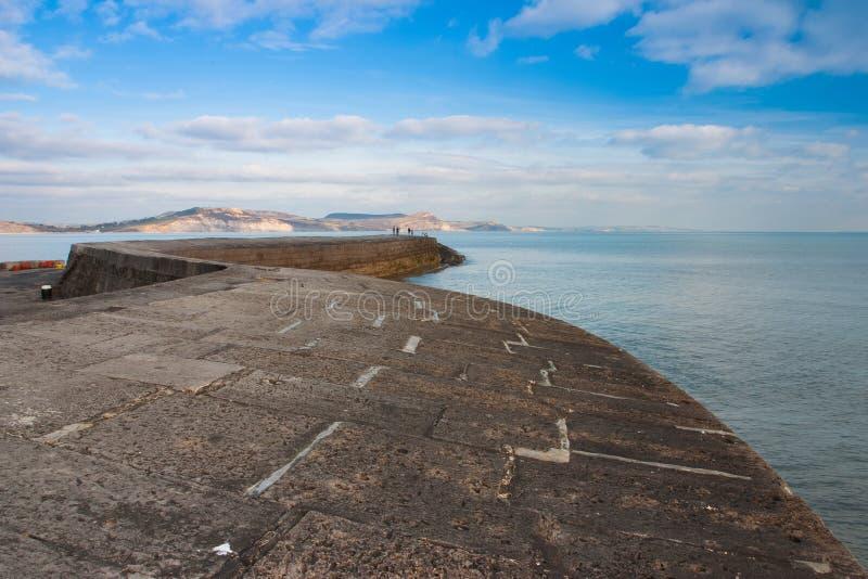 Den Cobb hamnväggen på Lyme Regis, Dorset arkivfoto